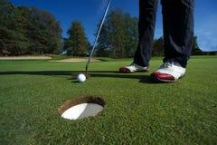 Schließen Sie oben von der Person, die Golfball auf Golfplatz setzt Stockfoto