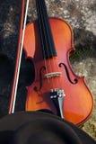 Schließen Sie oben von der Violine und Cowboyhut und Boulder. Stockbilder