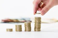 Schließen Sie oben von der weiblichen Hand, welche die ein-Euro-Münzen in zunehmende Spalten stapelt Stockfotografie