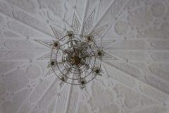 Schließen Sie oben von einer hängenden Lampe und von einer weißen Decke Stockfoto
