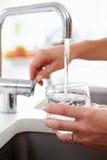 Schließen Sie oben von Frauen-strömendem Glas Wasser vom Hahn in der Küche Stockbild