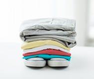 Schließen Sie oben von gefalteten Hemden und von Stiefeln auf Tabelle Lizenzfreies Stockbild