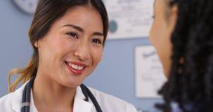 Schließen Sie oben von glücklichem asiatischem Doktor, der Patienten betrachtet Stockfoto