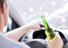 Schließen Sie oben von trinkendem Alkohol des Mannes beim Fahren des Autos Stockbild