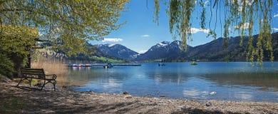Schliersee pittorico della riva del lago con il banco Fotografia Stock