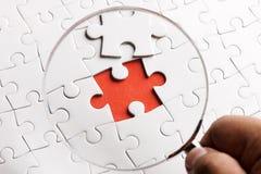 SCHLIESSEN Sie HERAUF Puzzlespielstücke mit einer Lupe. Konzeptbild der Entdeckung eines Defektes. lizenzfreies stockbild