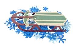 Schlitten auf einem Bett der bunten Schneeflocken Stockbilder