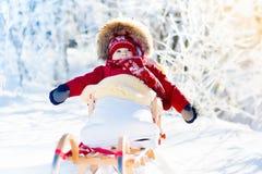 Schlitten- und Schneespaß für Kinder Baby, das im Winterpark rodelt Lizenzfreie Stockfotos
