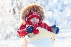 Schlitten- und Schneespaß für Kinder Baby, das im Winterpark rodelt Stockfoto