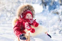 Schlitten- und Schneespaß für Kinder Baby, das im Winterpark rodelt Stockfotos