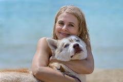 Schlittenhund und Blondine Stockfotos