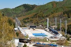Schlittschuh laufen der Eisbahn in den Bergen, Kasachstan Eisschnelllauf im Freien und gekrümmte Eisbahn in einem Gebirgstal Lizenzfreie Stockfotos