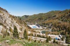 Schlittschuh laufen der Eisbahn in den Bergen, Kasachstan Eisschnelllauf im Freien und gekrümmte Eisbahn in einem Gebirgstal Lizenzfreies Stockbild