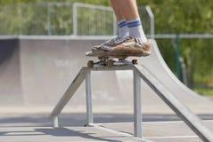 Schlittschuhläufer, der Schleifen 50-50 auf Spaßkasten im skatepark tut Stockfoto