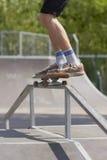 Schlittschuhläufer, der Schleifen 50-50 auf Spaßkasten im skatepark tut Stockfotografie