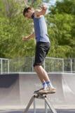 Schlittschuhläufer, der Schleifen 50-50 auf Spaßkasten im skatepark tut Lizenzfreies Stockfoto