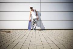 Schlittschuhläufer, der seins Skateboard anhält Stockbilder