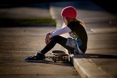 Schlittschuhläufer-Mädchen auf Beschränkung mit Skateboard Stockfotografie