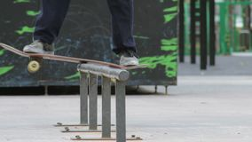Schlittschuhläufer machen frontside boardslide auf Schiene im skatepark, die Großaufnahme, slowmotion stock video