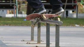 Schlittschuhläufer machen Schleifen schwache 180 auf Schiene im skatepark, Großaufnahme in slowmotion stock footage