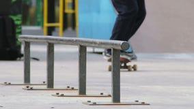 Schlittschuhläufer machen Schleifen schwache 180 auf Schiene im skatepark, Großaufnahme in slowmotion stock video footage