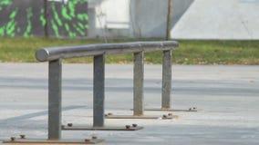 Schlittschuhläufer machen Trick boardslide auf Schiene im skatepark, Großaufnahme in slowmotion stock video