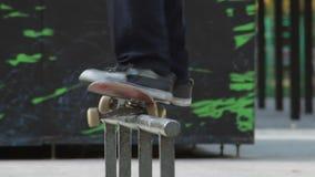Schlittschuhläufer springen auf eine Schiene mit Schleifen des Tricks 50-50, ausführliche Ansicht in slowmotion stock video footage