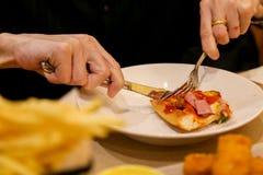 Schlitzen Sie die Käsepizza auf, indem Sie Messer und Völker verwenden stockfoto