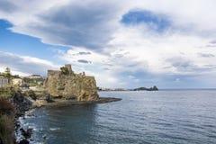 Schloss Aci Castello mit Acitrezza-Hintergrund Lizenzfreie Stockfotografie