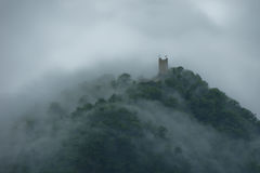 Schloss auf dem Berg in einem Nebel Lizenzfreie Stockfotos