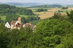 Schloss Blumenberg unter Bergen und Ackerland Stockbilder