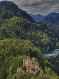 Schloss Hohenschwangau. With lake and forest, the castle viewed from above, with the Bavarian Alps in the background Royalty Free Stock Images