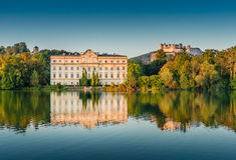 Schloss Leopoldskron com a fortaleza de Hohensalzburg em Salzburg no por do sol, Áustria Imagens de Stock