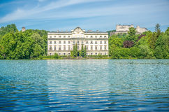 Schloss Leopoldskron with Hohensalzburg Fortress in Salzburg, Austria. Famous Schloss Leopoldskron with Hohensalzburg Fortress in the background on a sunny day royalty free stock images