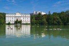 Schloss Leopoldskron mit Hohensalzburg-Festung im Hintergrund an einem sonnigen Tag in Salzburg, Österreich stockfotografie
