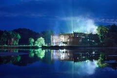 Schloss nachts umgeben durch einen Burggraben Stockbilder