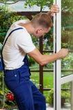 Schlosser, der eine Fensterkurbel justiert stockfoto