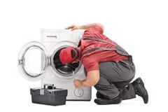 Schlosser, der eine Waschmaschine überprüft Stockbild