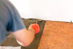 Schlosser, der Keramikfliesen legt Stockbilder