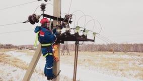 Schlosser, der an der Stromleitung mit Spannungsdrähten auf Station arbeitet stock video footage