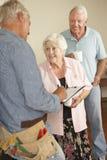 Schlosser-Giving Senior Couple-Schätzung für Reparatur Stockfotos