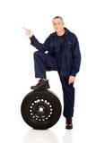 Schlosser mit dem Bein auf einem Reifen zeigend nach links Stockbild