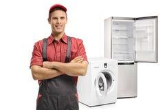 Schlosser mit seinen Armen faltete sich vor einer Waschmaschine und Stockfotografie
