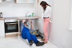 Schlosser-Repairing Pipe While-Frau in der Küche Stockfotografie