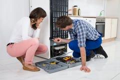 Schlosser Repairing Refrigerator Lizenzfreie Stockbilder