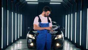 Schlosser schreibt auf ein Klemmbrett auf einem Autohintergrund Arbeitskraft steht in einer Garage und hält ein Klemmbrett und ei stock video