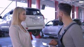 Schlosser- und Kundenfrau steht über Fahrzeugreparaturen auf Hintergrund des steigenden Autos auf Aufzug am Service in Verbindung stock footage