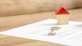 Schlüssellügen des silbernen Hauses auf einem Vertrag des Hausverkaufs Lizenzfreies Stockbild