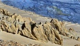Schlucht zum Hochgebirge: zum Vorderteil der gelbe sandige Bergabhang mit Steinidolen und hinter dem blauen Flussbett mit numerou Stockfotos