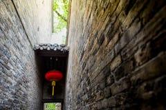 Schmale Backsteinmauer mit chinesischer roter Lampe, alte Wand des China-Dorfparks Lizenzfreies Stockfoto